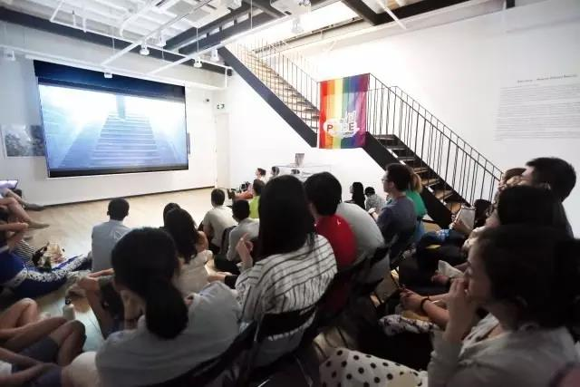 audience watching stairs scene with pride flag